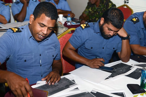 Second Lt. Deon Lendor (left) and 2nd Lt. Chris Persad, Trinidad & Tobago Coast Guard, work on an exercise to determine solar cell energy requirements for an existing building July 11.