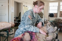 "Army Reserve 1st Lt. Rebecca Milligan, of the Effects and Enablers Team, which is augmenting the 84th Training Command's Combat Support Training Exercise and the Army Medical Command's Global Medic Exercise headquartered out of Fort Hunter Liggett, California, prepares ""Trauma Charlie"" a simulation injury mannequin used by medical professionals to train on during mass casualty scenarios on Camp Roberts, California, July 16, 2017."