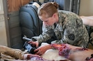 """Army Reserve 1st Lt. Rebecca Milligan, of the Effects and Enablers Team, which is augmenting the 84th Training Command's Combat Support Training Exercise and the Army Medical Command's Global Medic Exercise headquartered out of Fort Hunter Liggett, California, prepares """"Trauma Charlie"""" a simulation injury mannequin used by medical professionals to train on during mass casualty scenarios on Camp Roberts, California, July 16, 2017."""