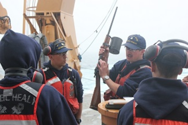 BM2 Jim Bowell instructs HEALY crewmembers on the use of the Shoulder Line Throwing Gun.