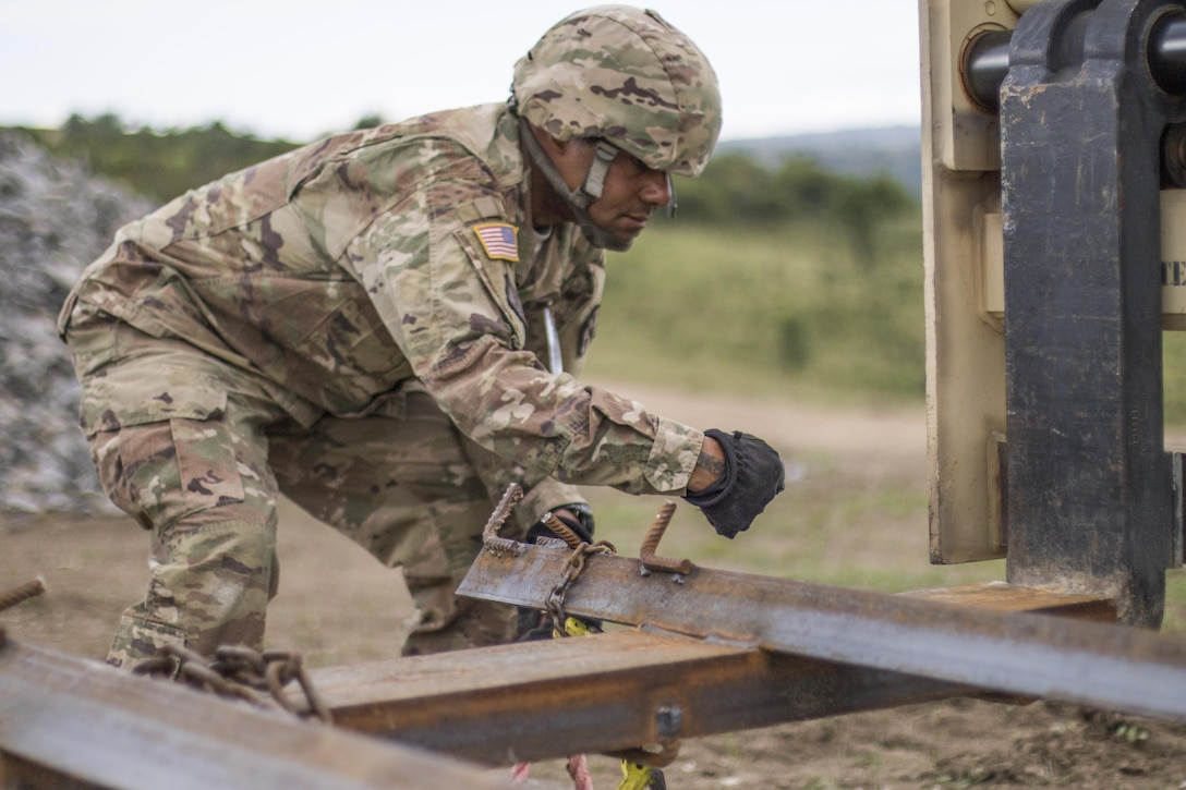 U.S. Army Reserve Soldier, Staff Sgt. Matthew Chisholm, Waycross, Ga., 381st Engineer Company, Tifton, Ga., helps prepare movement of construction materials during Resolute Castle 17 at Cincu, Romania, July 15, 2017. Chisholm, who works in Law, traveled from his home in Way Cross, Ga., with his unit to help complete construction of a new training facility that will provide Allied forces the opportunity to prepare for potential conflict. The entire operation is led by U.S. Army Reserve engineers, who moved Soldiers and equipment from the U.S. to Romania over a period of several weeks to complete the training facility. Resolute Castle improves interoperability, enhances confidence and security assurance between partner nations, while improving infrastructure, capability and capacity at select locations throughout Europe. (U.S. Army Reserve photo by Staff Sgt. Felix R. Fimbres)