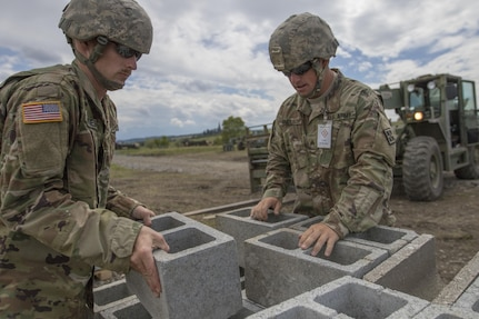 U.S. Army Reserve Soldiers Sgt. Travis Snelson, left, and Sgt. Byron Haynes, 733rd Engineer Company, Greenville, Tenn., prepare cinder blocks for transportation to another site during Resolute Castle 17, at Cincu, Romania, July 15, 2017. Snelson, who owns a landscaping company in Asheville, N.C., and Haynes, who is a highway inspector for the State of South Carolina as a contractor, are helping complete the construction of a training facility that will be used by allied forces throughout Europe. The entire operation is led by U.S. Army Reserve engineers, who moved Soldiers and equipment from the U.S. to Romania over a period of several weeks to complete the training facility. Resolute Castle improves interoperability, enhances confidence and security assurance between partner nations, while improving infrastructure, capability and capacity at select locations throughout Europe. (U.S. Army Reserve photo by Staff Sgt. Felix R. Fimbres)