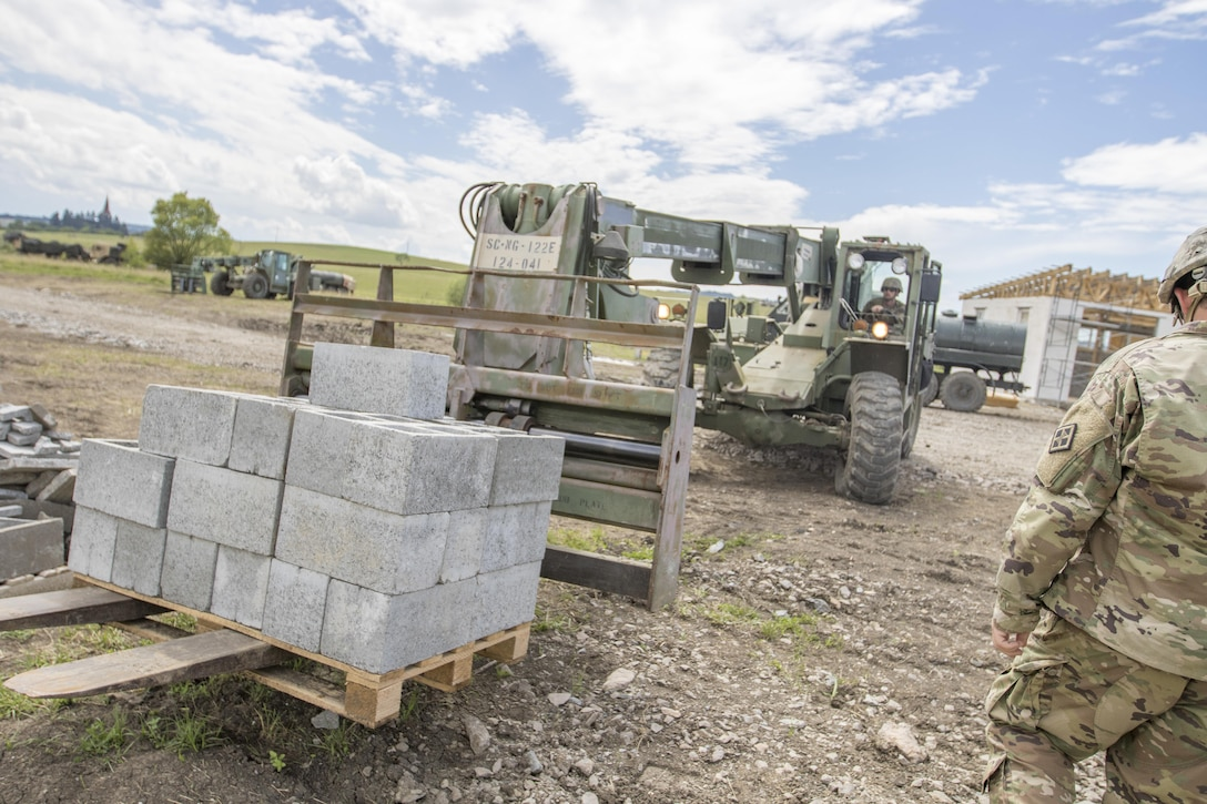 U.S. Army Reserve Soldier, Sgt. Travis Snelson, Asheville, N.C., 733rd Engineer Company Greenville, S.C., uses construction equipment to move a pallet of cinder blocks during Resolute Castle 17 at Cincu, Romania, July 15, 2017. Snelson, who owns a landscaping company in Asheville, N.C, traveled to Romania with his unit to help complete construction of a new training facility that will provide Allied forces the opportunity to prepare for potential conflict. The entire operation is led by U.S. Army Reserve engineers, who moved Soldiers and equipment from the U.S. to Romania over a period of several weeks to complete the training facility. Resolute Castle improves interoperability, enhances confidence and security assurance between partner nations, while improving infrastructure, capability and capacity at select locations throughout Europe. (U.S. Army Reserve photo by Staff Sgt. Felix R. Fimbres)