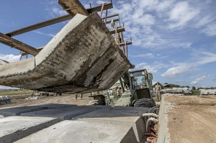 Sgt. Alex Head, 390th Engineer Company Chattanooga, Tenn., moves concreate slabs during Resolute Castle 17 at Cincu, Romania, July 15, 2017. These slabs will be used as firing positions for tanks at the training facility Head is helping construct. The facility will provide Allied forces the opportunity to prepare for potential conflict. The entire operation is led by U.S. Army Reserve engineers, who moved Soldiers and equipment from the U.S. to Romania over a period of several weeks to complete the training facility. Resolute Castle improves interoperability, enhances confidence and security assurance between partner nations, while improving infrastructure, capability and capacity at select locations throughout Europe. (U.S. Army Reserve photo by Staff Sgt. Felix R. Fimbres)