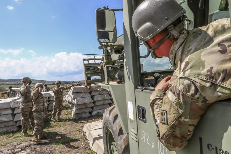 Sgt. Alex Head, 390th Engineer Company, Chattanooga, Tenn., moves concreate slabs during Resolute Castle 17 at Cincu, Romania, July 15, 2017. These slabs will be used as firing positions for tanks at the training facility Head is helping construct. The facility will provide Allied forces the opportunity to prepare for potential conflict. The entire operation is led by U.S. Army Reserve engineers, who moved Soldiers and equipment from the U.S. to Romania over a period of several weeks to complete the training facility. Resolute Castle improves interoperability, enhances confidence and security assurance between partner nations, while improving infrastructure, capability and capacity at select locations throughout Europe. (U.S. Army Reserve photo by Staff Sgt. Felix R. Fimbres)