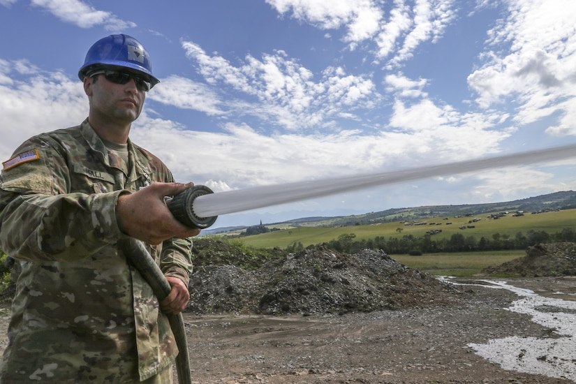 U.S. Army Reserve Soldier, Spc. Jordy Hall, 390th Engineer Company, Chattanooga, Tenn., washes down construction equipment, part of routine maintenance, during Resolute Castle 17 at Cincu, Romania, July 15, 2017. Hall, who works at a Walmart Distribution Center, Greenville, Tenn., has traveled from his home in Greenville, Tenn., with his unit to help complete construction of a new training facility that will provide Allied forces the opportunity to prepare for potential conflict. The entire operation is led by U.S. Army Reserve engineers, who moved Soldiers and equipment from the U.S. to Romania over a period of several weeks to complete the training facility. Resolute Castle improves interoperability, enhances confidence and security assurance between partner nations, while improving infrastructure, capability and capacity at select locations throughout Europe. (U.S. Army Reserve photo by Staff Sgt. Felix R. Fimbres)
