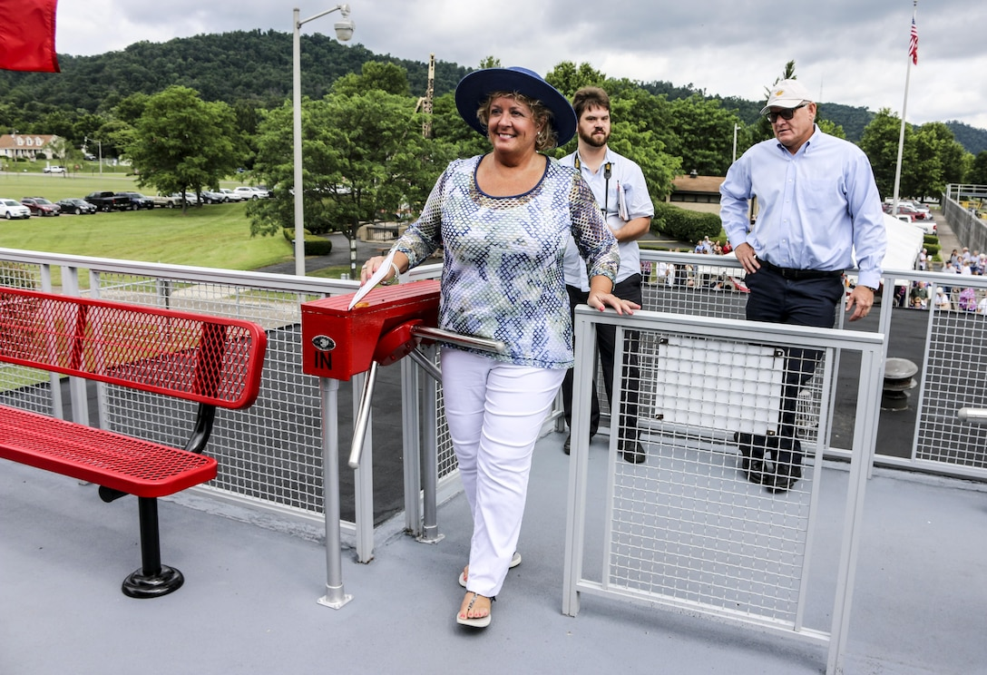 As one of the first visitors at the newly renovated visitors center, Ms. Hoagland, the wife of Frank Hoagland, Ohio 30th District Senator (far right), goes through the turnstile at Hannibal Lock and Dam.