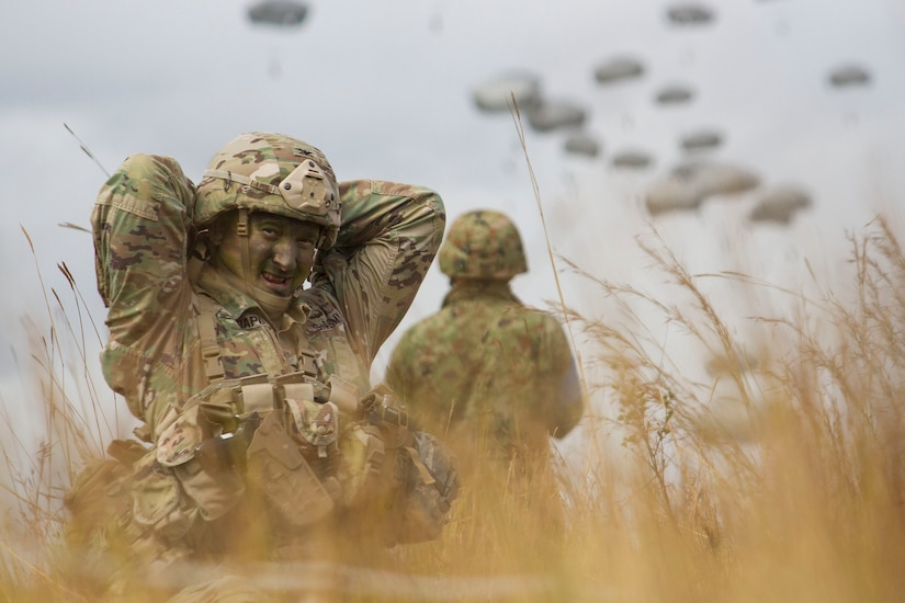 Army Col. Jeffrey Crapo, commander of the 4th Infantry Brigade Combat Team, 25th Infrantry Division, adjusts his gear after landing at Drop Zone Kapyong near Williamson Airfield at Shoalwater Bay Training Area, Australia, July 13, 2017. Washington Army National Guard photo by Staff Sgt. Rory Featherston