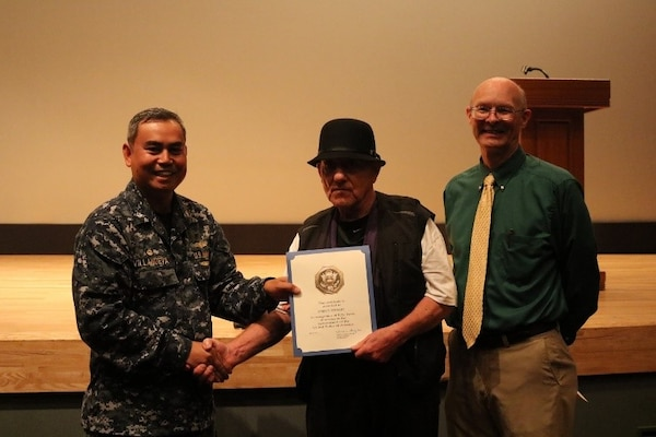 James Stewart, center, Receiving Branch materiel handler, is presented a 50-year Federal service certificate, pin and letter on behalf of the DLA Director by DLA Distribution Yokosuka, Japan, commanding officer Cmdr. Nolasco Villanueva, left, and deputy commander Roy Jewell.