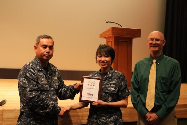 Petty Officer Xiaoyang Xing, center, receives the Combined Federal Campaign Gold Award from DLA Distribution Yokosuka, Japan, commanding officer Cmdr. Nolasco Villanueva, left, and deputy commander Roy Jewell.  At the same time, she was announced as the Meritorious Advancement Program selectee, advancing her to First Class Petty Officer.