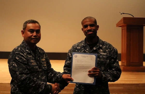 DLA Distribution Yokosuka, Japan, commanding officer Navy Cmdr. Nolasco Villanueva advances Petty Officer Kevin R. Craig Jr. to Second Class Petty Officer.