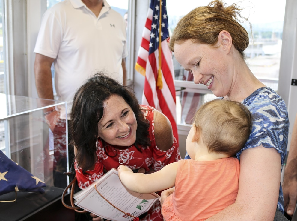 Stacy Lloyd, district commander's wife, greets one of the youngest visitors at the Hannibal Lock and Dam visitor's center, July 1.