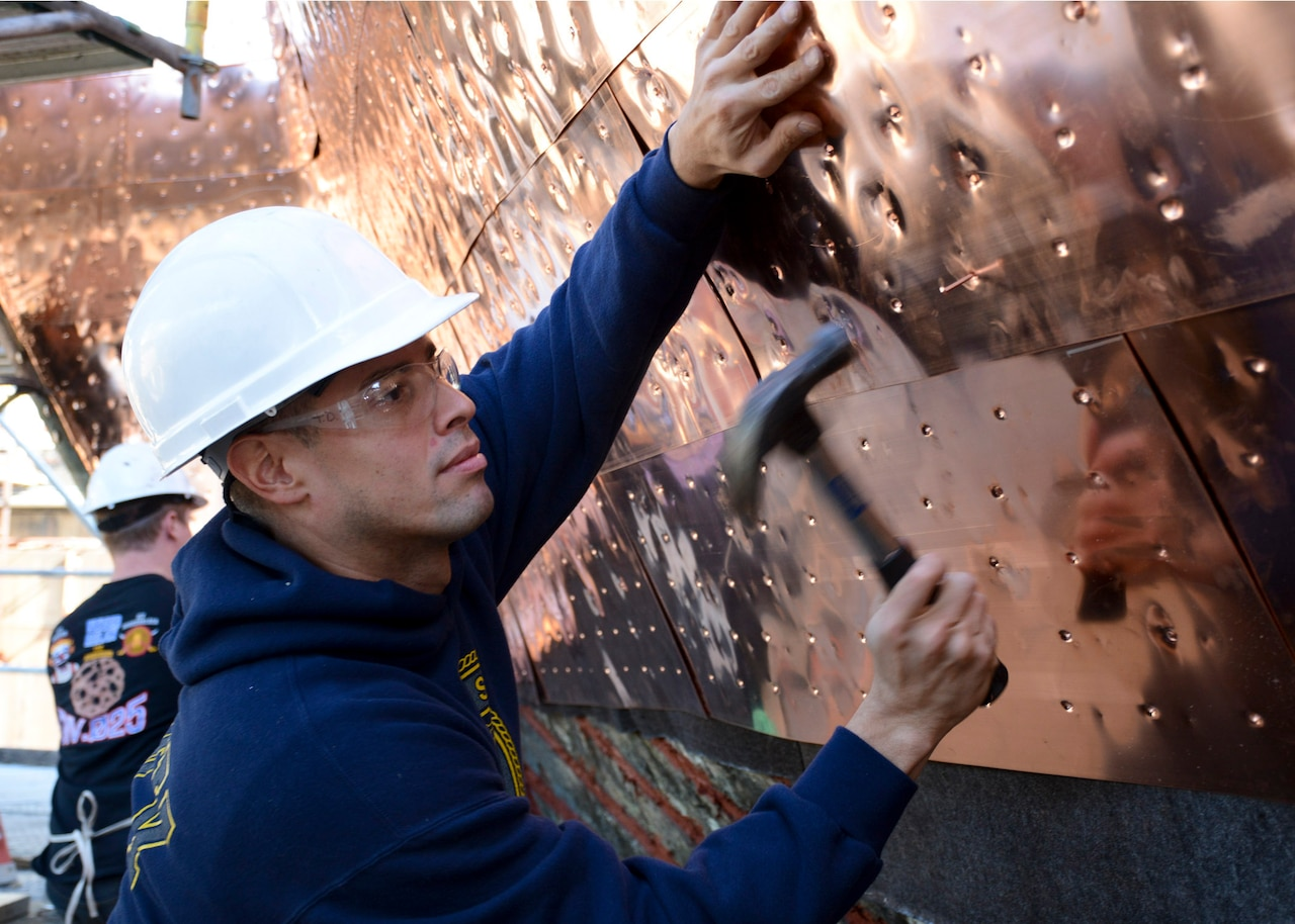 Navy Petty Officer 3rd Class Jorge Ortiz, assigned to the USS Constitution, hammers a copper nail into the new copper sheets that line the hull of the ship, which is dry docked in the Charlestown Navy Yard in Boston, Oct. 20, 2016. The USS Constitution was undergoing a multiyear restoration in Dry Dock 1, the second oldest dry dock in the United States. Navy photo by Petty Officer 3rd Class William Collins III
