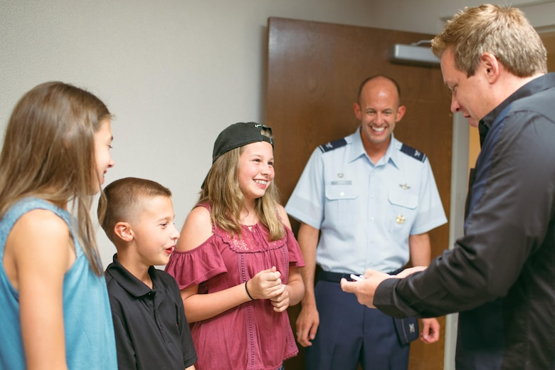 Magician Mike Super performs a card trick for Col. E. John Teichert, 11th Wing and Joint Base Andrews commander, and family at JBA, Md., July 21, 2017. During his 17-installation tour, Super said that he was looking forward to meeting Airmen and families, learning more about Air Force career fields and spending time on installations. (U.S. Air Force photo by Senior Airman Delano Scott)
