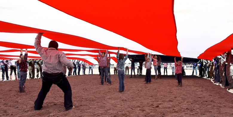 Children from the community stand under the American flag to keep it off the ground during Military Monday at Frontier Park in Cheyenne, Wyo., July 24, 2017. The flag presentation is an annual tradition at Cheyenne Frontier Days. This year marks the 150th anniversary of F.E. Warren Air Force Base and the city of Cheyenne. The two communities came together to celebrate during the 121st CFD rodeo and festival. (U.S. Air Force photo by Airman 1st Class Braydon Williams)