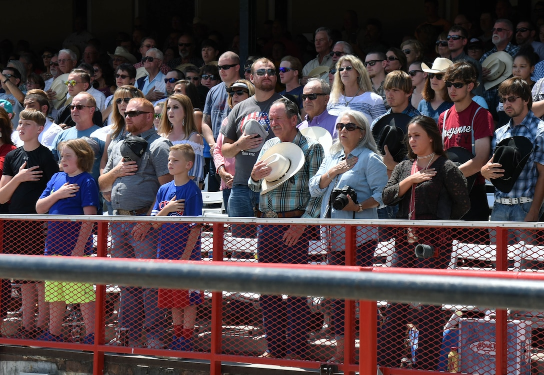 Spectators stand for the national anthem during Military Monday at Frontier Park in Cheyenne, Wyo., July 24, 2017. Cheyenne Frontier Days is Cheyenne's biggest annual event with hundreds of visitors taking part. This year marks the 150th anniversary of F.E. Warren Air Force Base and the city of Cheyenne. The two communities came together to celebrate during the 121st CFD rodeo and festival. (U.S. Air Force photo by Airman 1st Class Breanna Carter)