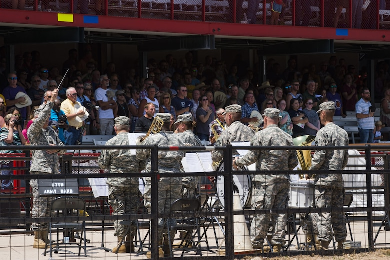 The 67th Army Band, Wyoming National Guard, plays the national anthem during Military Monday at Frontier Park in Cheyenne, Wyo., July 24, 2017. While the anthem played, more than 100 volunteers unfurled a massive flag to begin the rodeo's grand entry ceremony. This year marks the 150th anniversary of F.E. Warren Air Force Base and the city of Cheyenne. The two communities came together to celebrate during the 121st Cheyenne Frontier Days rodeo and festival. (U.S. Air Force photo by Staff Sgt. Christopher Ruano)
