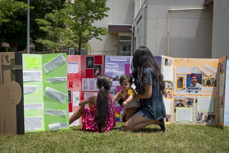 A family reads information posters about the history of the modern military and non-military Lesbian, Gay, Bisexual and Transgender community during the LGBT BBQ Field Day event, June 6, 2017, at Yokota Air Base, Japan. The informational posters were made by members of the LGBT community and were displayed at the LGBT Pride events; they ranged in topics from: LGBT rights through history, influential members in the LGBT community, miscellaneous facts, a glossary of LGBT terms, coming out stories and much more. (U.S. Air Force photo by Airman 1st Class Donald Hudson)