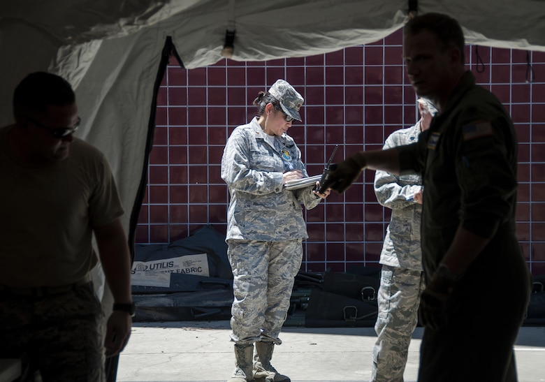 Maj. Theresa Sun-Isbell, 349th Aeromedical Staging Squadron wing inspection team lead, observes members of the ASTS partake in a humanitarian aid scenario as part of Patriot Wyvern at Travis Air Force Base, Cali., on July 22, 2017. The 349th ASTS members had one hour to set up an En-Route Patient Staging Facility and communications. They accomplished their task in less than 30 minutes. (U.S. Air Force photo by Staff Sgt. Daniel Phelps)