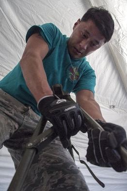 Maj. Teh Lee, 349th Aeromedical Staging Squadron clinical nurse, puts together cots during Patriot Wyvern at Travis Air Force Base, Calif., July 22, 2017. The 349th ASTS members had one hour to set up the En-Route Patient Staging Facility and accomplished their task in 35 minutes. (U.S. Air Force photo by Staff Sgt. Daniel Phelps)