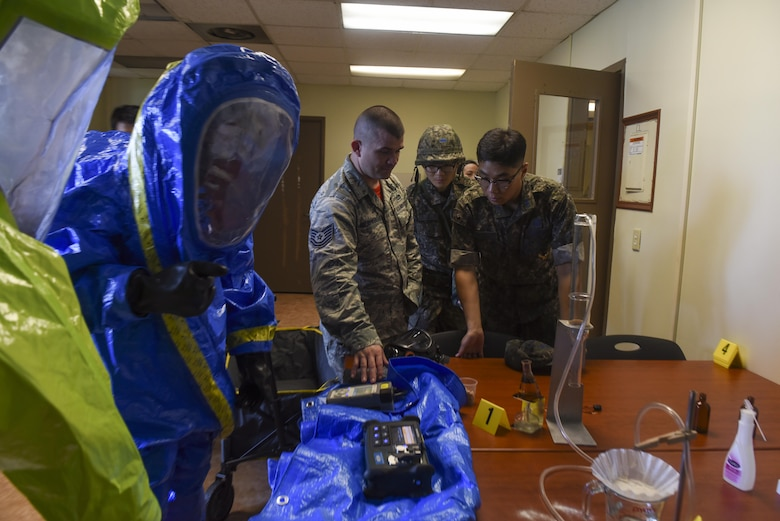 U.S. Air Force Tech. Sgt. Joseph Neejer-Widener, 8th Civil Engineer Squadron emergency management flight noncommissioned officer in charge, center, shows Republic of Korea Air Force Lt. Kim, Kitae, 38th Fighter Group chemical, biological, radiological, and nuclear defense support flight commander, different tools to detect and define substances while performing response operations for a hazardous material incident at Kunsan Air Base, Republic of Korea, July 21, 2017. The training scenario gave participants a better understanding of HAZMAT response equipment and operations. (U.S. Air Force photo by Senior Airman Michael Hunsaker/ Released)