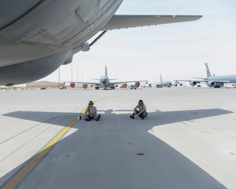 U.S. Air Force Technical Sgt. Korey Barber, left, crew chief, and Airman 1st Class Cormac Miller, right, hydraulic apprentice, both assigned to the 340th Expeditionary Aircraft Maintenance Unit, find a bit of shade beneath the tail of a KC-135 Stratotanker as they wait for final preparations prior to launching the aircraft from Al Udeid, Air Base, Qatar, July 7, 2017. The members of the 340th and 22nd EAMUs face minute-by-minute challenges in the sweltering heat on the runway as they work to keep a fleet of KC-135 Stratotankers ready to fly. (U.S. Air National Guard photo by Tech. Sgt. Bradly A. Schneider/Released)