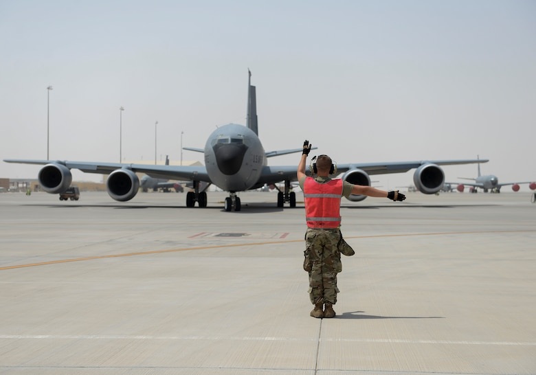 U.S. Air Force Staff Sgt. Benjamin Wolford, crew chief assigned to the 340th Expeditionary Aircraft Maintenance Unit, marshals a KC-135 to the runway at Al Udeid, Air Base, Qatar, July 7, 2017. The members of the 340th and 22nd EAMUs face minute-by-minute challenges in the sweltering heat on the runway as they work to keep a fleet of KC-135 Stratotankers ready to fly. (U.S. Air National Guard photo by Tech. Sgt. Bradly A. Schneider/Released)