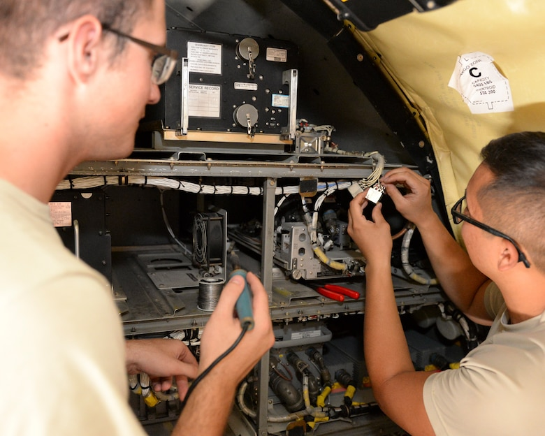 U.S. Air Force Airman 1st Class Thomas Doane, left, guidance and control apprentice, and Senior Airman Tony Nguyen, guidance and control journeyman, both assigned to the 340th Expeditionary Aircraft Maintenance Unit, prepare to solder a power control relay on a KC-135 Stratotanker at Al Udeid, Air Base, Qatar, July 7, 2017. The members of the 340th and 22nd EAMUs face minute-by-minute challenges in the sweltering heat on the runway as they work to keep a fleet of KC-135 Stratotankers ready to fly. (U.S. Air National Guard photo by Tech. Sgt. Bradly A. Schneider/Released)
