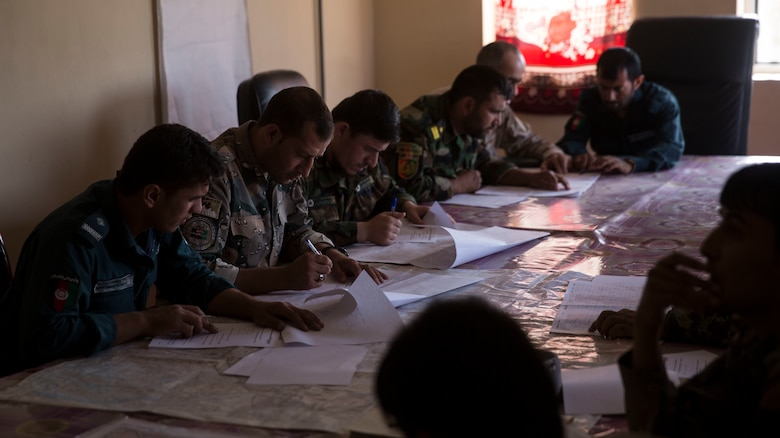 Afghan National Defense and Security Force partners take a map reading test at Bost Airfield, Afghanistan, July 16, 2017. U.S. Marine advisors with Task Force Southwest conducted a three-week map reading class focusing on terrain association, plotting and finding grid coordinates on a map. (U.S. Marine Corps photo by Justin T. Updegraff)