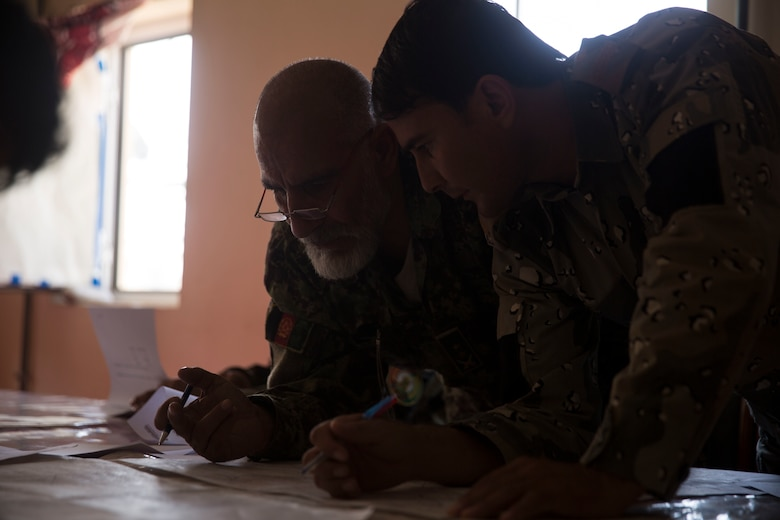 Afghan National Defense and Security Force partners create a six-digit grid based off of a given terrain feature during a map reading test at Bost Airfield, Afghanistan, July 16, 2017. U.S. Marine advisors with Task Force Southwest conducted a three-week map reading class focusing on terrain association, plotting and finding grid coordinates on a map. (U.S. Marine Corps photo by Justin T. Updegraff)