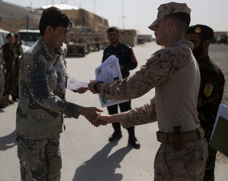 An Afghan National Civil Order Policeman receives his certificate for passing a map class at Bost Airfield, Afghanistan, July 22, 2017. U.S. Marine advisors with Task Force Southwest conducted a three-week map reading class focusing on terrain association, plotting and finding grid coordinates on a map. (U.S. Marine Corps photo by Justin T. Updegraff)