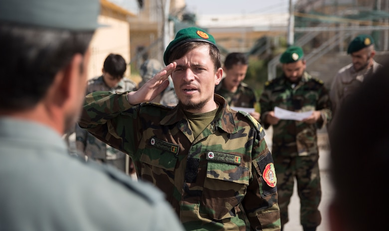 An Afghan National Army soldier steps up to receive his certificate for graduating a map reading class at Bost Airfield, Afghanistan, July 22, 2017. With assistance from U.S. Marine advisors with Task Force Southwest, the three-week course covered multiple areas including measuring straight and curved line distances, as well as being able to plot and pull a six-digit grid from a map. (U.S. Marine Corps photo by Justin T. Updegraff)
