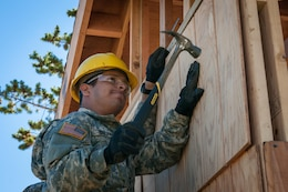 U.S. Army Reserve Pfc. Edgar Briones, a plumber, from the 994th Engineer Company out of Denver, Colorado, installs siding during the construction of a large storage shed at the YMCA of the Rockies-Snow Mountain Ranch, in Granby, Colorado, July 20, 2017. (U.S. Army Reserve photo by Spc. Ce Shi, 222nd Broadcast Public Affairs Detachment)