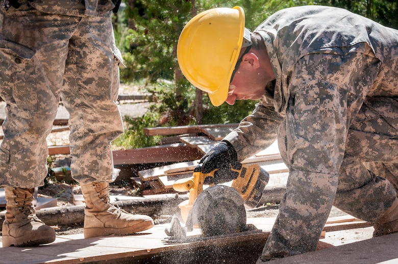 U.S. Army Reserve Spc. Gage Dean, a carpentry and masonry specialists with the 409th Engineer Company out of Fort Collins, Colorado, cuts siding during the construction of a large storage shed at the YMCA of the Rockies - Snow Mountain Ranch, in Granby, Colorado, July 17, 2017. (U.S. Army Reserve photo by Spc. Ce Shi, 222nd Broadcast Public Affairs Detachment)