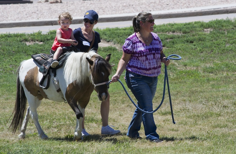 SCHRIEVER AIR FORCE BASE, Colo. -- Isabelle Scarlett Grissman, accompanied by her mom, Bonnie, rides a pony at Schriever's 2017 Summer Slam Picnic on Friday, July 21, 2017. Previous years offered elephant and camel rides to Airmen and their families, the ponies were a new addition to this years picnic. (U.S. Air Force photo/Senior Airman Laura Turner)