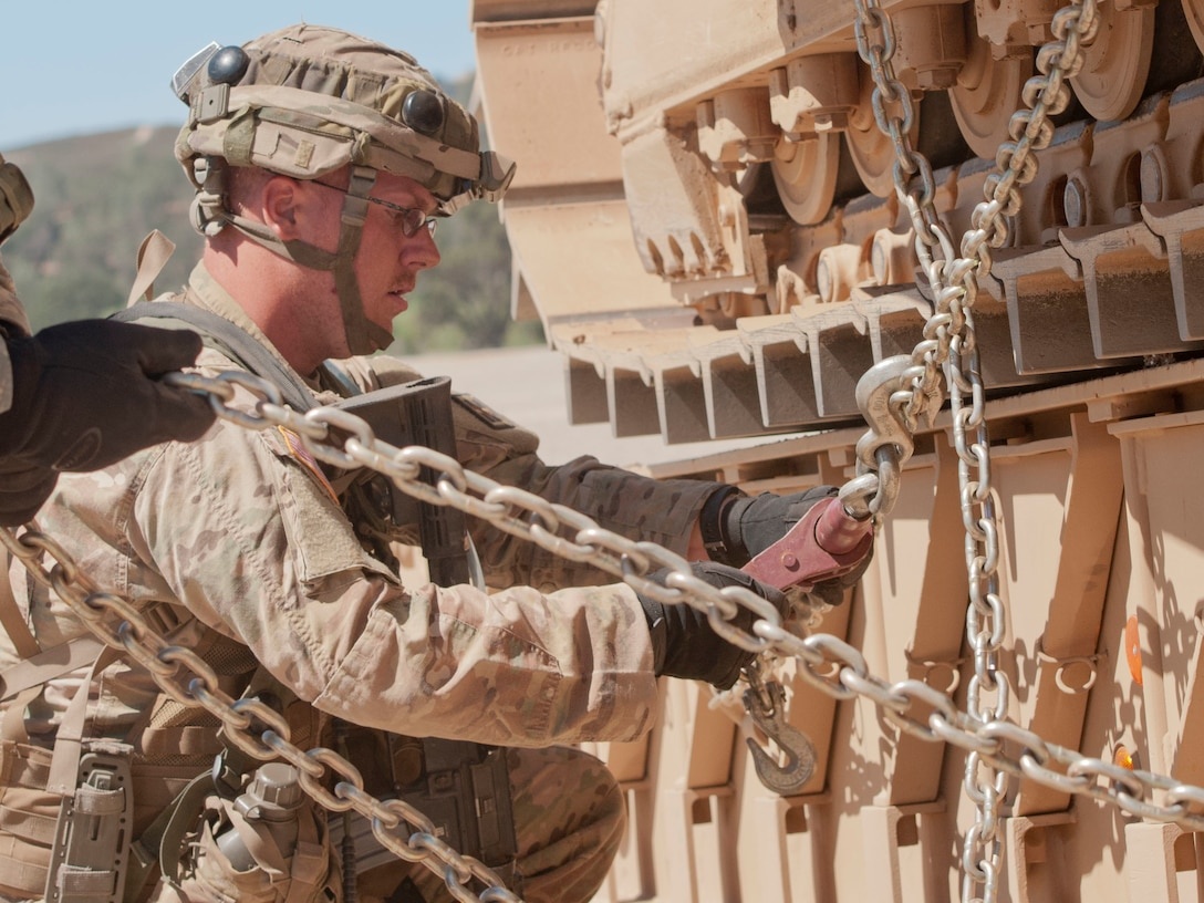 Army Reserve Sgt. John Brownlee, a horizontal construction engineer, removes chains from a Caterpillar D7R bulldozer during Combat Support Training Exercise 91-17-03 at Fort Hunter Liggett, Calif., on July 19, 2017. Brownlee is with the 718th Engineer Company out of Fort Benning, Ga. Nearly 5,400 service members from the U.S. Army Reserve, U.S. Army, Army National Guard, U.S. Navy, and Canadian Armed Forces are training at Fort Hunter Liggett, Calif., as part of the 84th Training Command's CSTX 91-17-03 and ARMEDCOM's Global Medic; this is a unique training opportunity that allows U.S. Army Reserve units to train alongside their multi-component and joint partners as part of the America's Army Reserve evolution into the most lethal Federal Reserve force in the history of the nation. (U.S. Army Reserve photo by Sgt. Thomas Crough, 301st Public Affairs Detachment)