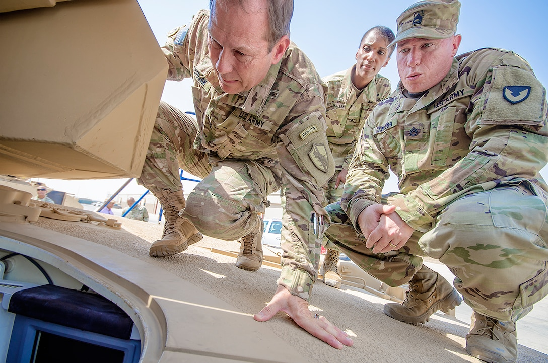 Maj. Gen. Edward Dorman (left), J-4 (logistics), U.S. Central Command, looks at a combat configured tank with Sgt. 1st Class Frank Taylor, contract officer representative, Army Field Support Battalion-Kuwait and Col. Carmelia Scott-Skillern, commander, 401st Army Field Support Brigade during a tour of an Army Prepositioned Stocks-5 warehouse at Camp Arifjan, Kuwait, July 20. (U.S. Army Photo by Justin Graff, 401st AFSB Public Affairs) (Photo Credit: U.S. Army)