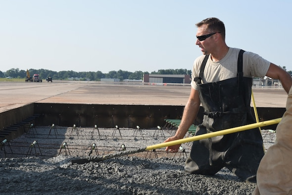 Staff Sgt. Jon Martinez, assigned to the 2nd Civil Engineer Squadron Dirt Boyz, stands in wet concrete as he evens it out at Barksdale Air Force Base, La., July 18, 2017. Martinez wore rubber overalls in order to keep the concrete's corrosive chemicals off his skin. (U.S. Air Force Photo/Airman 1st Class Sydney Bennett)