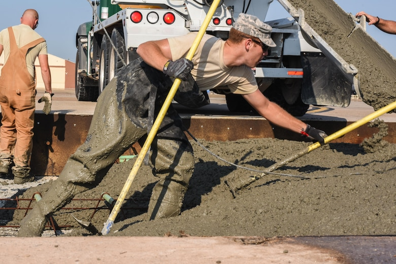 Staff Sgt. Zachary Aronin, assigned to the 2nd Civil Engineer Squadron Dirt Boyz, use rakes and shovels to spread wet concrete throughout a slab being fixed at Barksdale Air Force Base, La., July 18, 2017. The concrete replaced was over 35 years old. (U.S. Air Force Photo/Airman 1st Class Sydney Bennett)