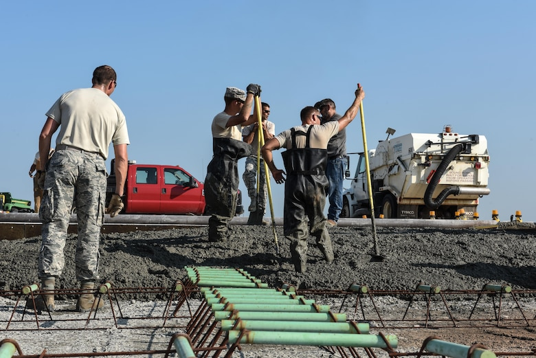 Dirt Boyz from the 2nd Civil Engineer Squadron wait for a concrete truck delivery at Barksdale Air Force Base, La., July 18, 2017. Each concrete truck contains approximately 10 yards worth of concrete. The open slab needed 106 yards. (U.S. Air Force Photo/Airman 1st Class Sydney Bennett)