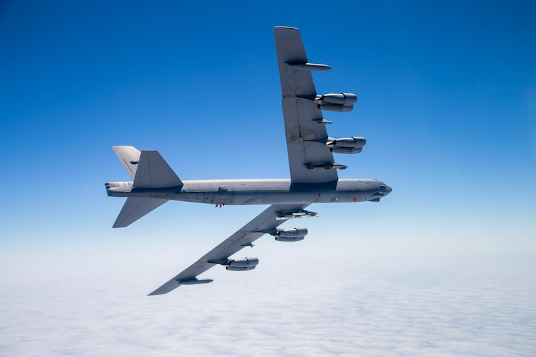 A B-52 Stratofortress assigned to the 419th Flight Test Squadron flies with eight PDU-5/B leaflet bombs connected to an external Heavy Stores Adapter Beam. (U.S. Air Force photo by Christopher Okula)