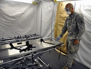 Spc. Christopher Myers, a mortuary affairs specialist with the 311th Quartermaster Company out Ramey Base, Puerto Rico, demonstrates the use of a special gurney, which is a component of the Mobile Integrated Remains Collection System at Fort Pickett, Virginia, July 16, 2017. The Army Reserve Soldier is participating in the 2017 Joint Mortuary Affairs Exercise along with active Army Soldiers, the Air Force and Marines.