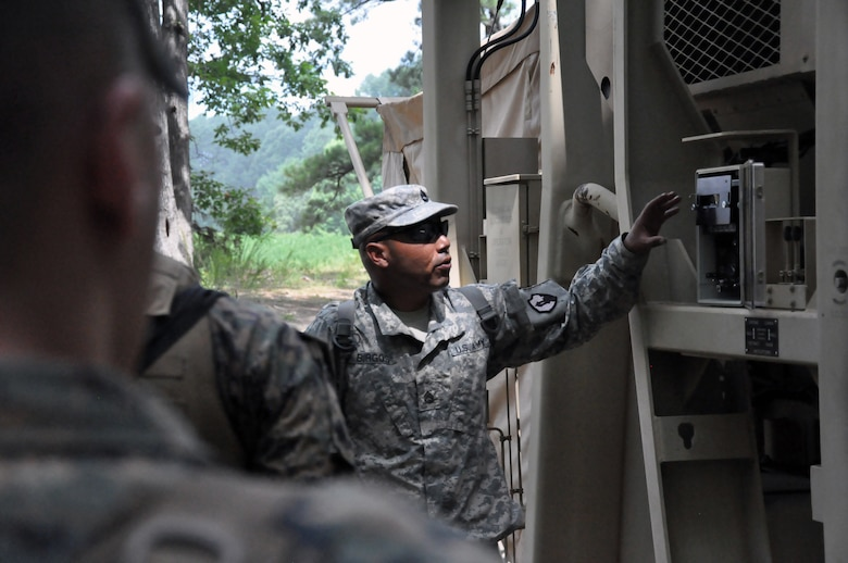 Sgt. 1st Class Luis Burgos, a mortuary affairs collection point NCOIC with the 311th Quartermaster Company out Ramey Base, Puerto Rico, shows a group of mortuary affairs Marines the cooling components outside a Mobile Integrated Remains Collection System at Fort Pickett, Virginia, July 17, 2017. The Army Reserve Soldier is participating in the 2017 Joint Mortuary Affairs Exercise along with active Army Soldiers, the Air Force and Marines.