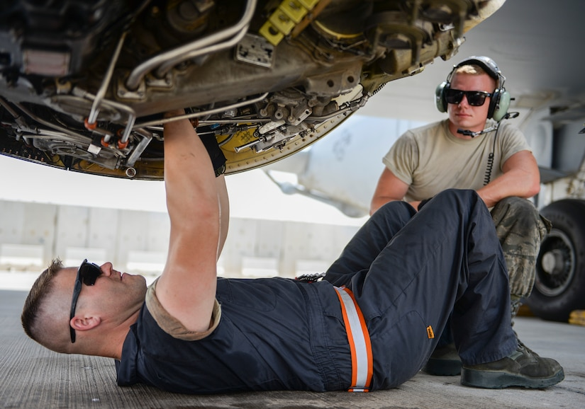 Air Force Staff Sgt. Kyle Craig, an aerospace propulsion journeyman, trims a main engine control on the engine of a KC-135 Stratotanker as Air Force Airman 1st Class Jared Suppes, an aerospace propulsion apprentice, provides support at Al Udied Air Base, Qatar, July 7, 2017. Air National Guard photo by Tech. Sgt. Bradly A. Schneider