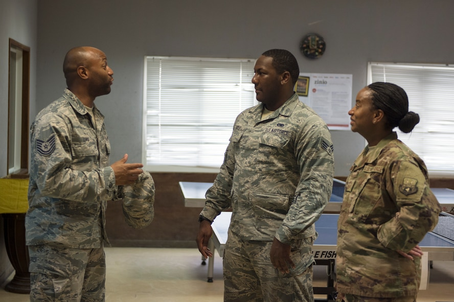 U.S. Air Force Senior Airman Quae Hayes, center, an analyst with the 379th Expeditionary Maintenance Group, listens to Tech. Sgt. Jermaine Lewis, a quality assurance evaluator with the 379th Expeditionary Forces Support Squadron, talk about the services that EFSS provides at Al Udeid Air Base, Qatar, July 14, 2017.  Hayes is taking part in a Chief Shadowing Program and was paired up with Chief Master Sgt. Gloria Weatherspoon, right, a chief enlisted manager with the 379th EFSS, for the day in order to receive a glimpse into the day-to-day actives of a Chief Master Sgt. in the U.S. Air Force. (U.S. Air Force photo by Tech. Sgt. Amy M. Lovgren)