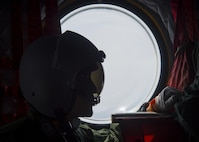 A Japan Air Self-Defense Force CH-47J crew chief assigned to the Air Reserve Wing, Flight Group Misawa Helicopter Airlift Squadron, looks out the window during a flight to Chitose Air Base, Japan, July 21, 2017. The ARW is located at JASDF Iruma Air Base, Japan, near the north of western Tokyo. The CH-47J was providing cargo to Chitose AB, which gave Pacific Air Forces' F-16 Demonstration Team members the opportunity to use this method of transportation. (U.S. Air Force Staff Sgt. Deana Heitzman)
