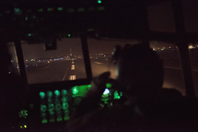 A pilot with the 737th Expeditionary Airlift Squadron looks out the window of a C-130H Hercules as the aircraft takes the runway behind another C-130 at an undisclosed location in Southwest Asia, July 14, 2017. Air National Guardsmen and their aircraft, deployed in support of Combined Joint Task Force – Operation Inherent Resolve, execute daily airlift missions out of one of the busiest air bases in the U.S. Air Forces Central Command area of responsibility. (U.S. Air Force photo by Tech. Sgt.  Jonathan Hehnly)