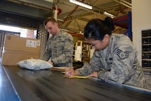 U.S. Air Force Staff Sgts. Douglas Eaton and Hyeyun Nam, 100th Communications Squadron Post Office postal clerks, work together to manually log in new parcels July 18, 2017, at RAF Mildenhall, England. The new system, scheduled to take effect Aug. 14, will allow email notifications to be sent to customers when their packages have arrived at the post office. (U.S. Air Force photo by Tech. Sgt. Lauren Gleason)