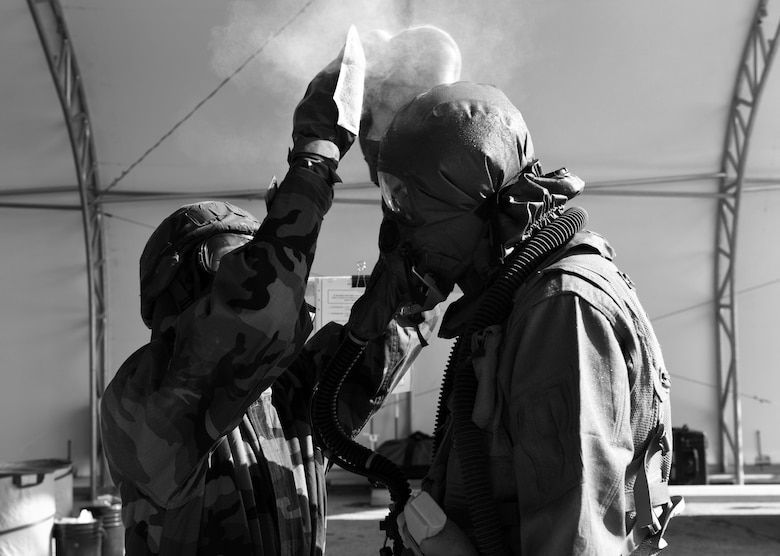 An aircrew flight equipment Airman uses M295 mitts to simulate removing contamination from an aircrew member during the Aircrew Contamination Control Area process as part of exercise Toxic Arch on at Scott Air Force Base, Ill., July 19. The M295 mitts are used to transfer as much charcoal to the aircrew member and equipment as possible. (U.S. Air Force photo by Tech. Sgt. Terri Paden)