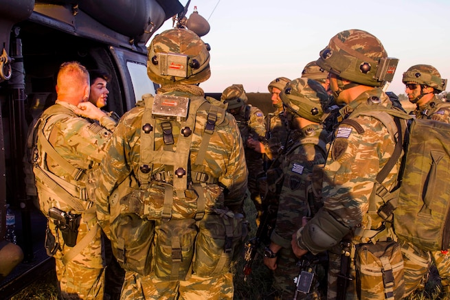 Army helicopter crew members, left, give a safety brief to Greek soldiers before participating in night air assault training during exercise Swift Response at Bezmer Air Base, Bulgaria, July 21, 2017. The exercise is part of Saber Guardian 17. Army photo by Spc. Thomas Scaggs